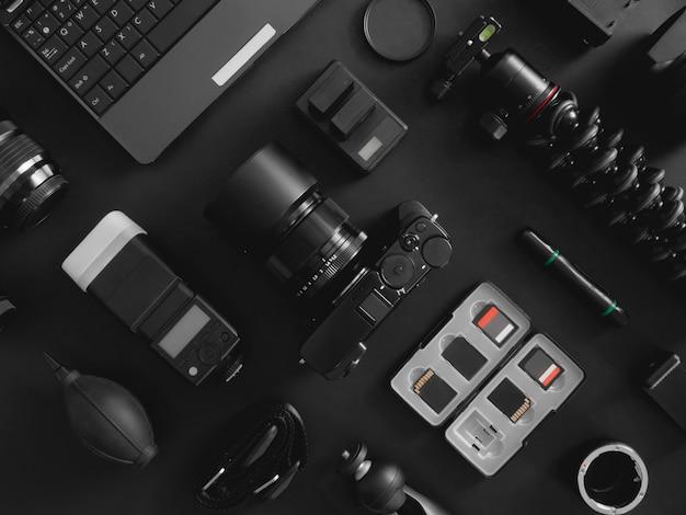 Vista superior del fotógrafo del espacio de trabajo con cámara digital, flash, kit de limpieza, tarjeta de memoria, trípode y accesorio de cámara sobre fondo negro de mesa