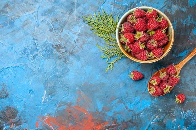Vista superior de frambuesas rojas dentro de la placa sobre fondo azul.