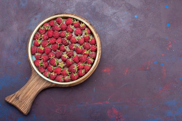 Vista superior de frambuesas rojas frescas bayas maduras sobre el fondo azul oscuro baya alimento de verano suave vitamina