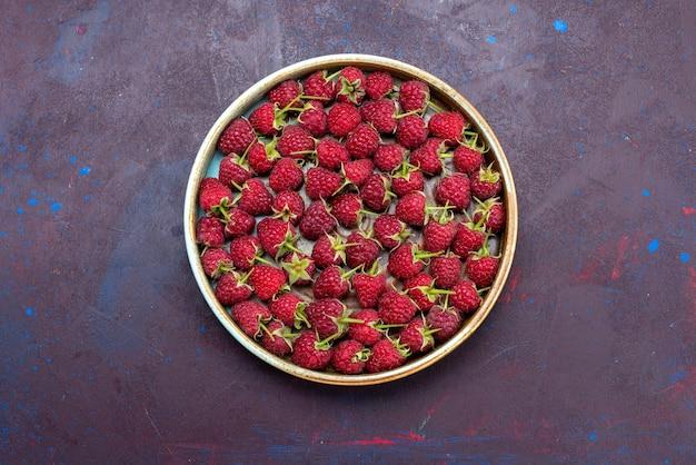 Vista superior frambuesas rojas frescas bayas maduras sobre fondo azul oscuro fruta suave vitamina comida de verano