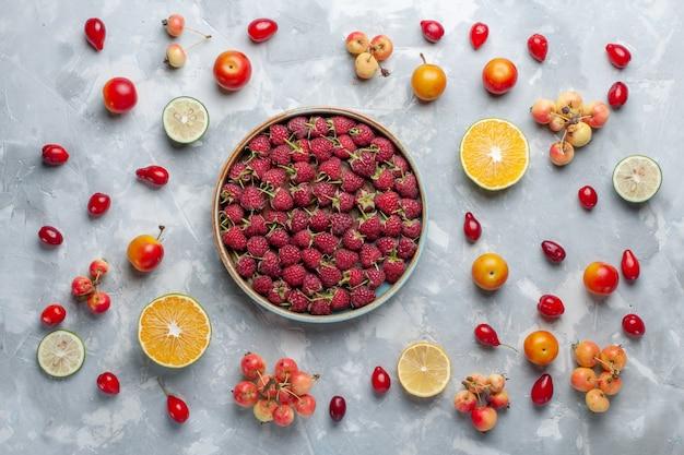 Vista superior de frambuesas rojas frescas con limón y cerezas en escritorio blanco fruta berry vitamina verano suave