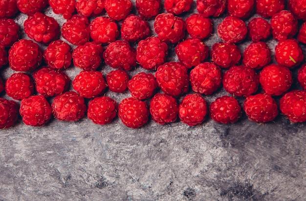 Vista superior de frambuesas rojas sobre una mesa gris oscuro