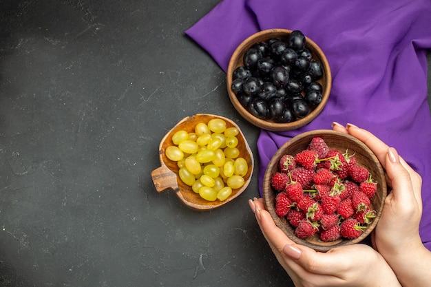 Vista superior de frambuesas en un tazón en manos femeninas uvas negras y amarillas en tazones mantón púrpura oscuro espacio libre de superficie aislada