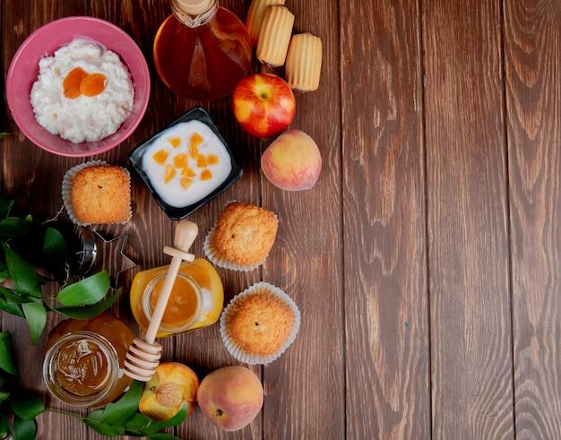 Vista superior de frascos de mermeladas como durazno y ciruela con pastelitos de duraznos queso cottage en madera decorada con hojas con espacio de copia