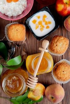 Vista superior de frascos de mermeladas como durazno y ciruela con pastelitos de duraznos requesón sobre madera