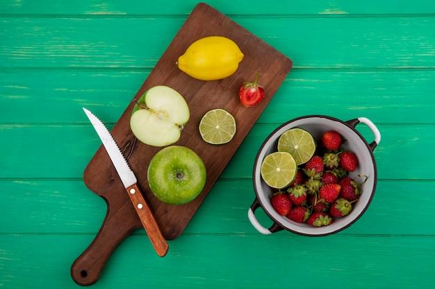 Vista superior de la fresa en una cacerola con cal de manzana sobre una tabla de cocina de madera sobre un fondo de madera verde