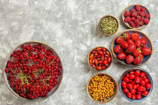 Vista superior de fresas frescas con arándanos sobre un fondo blanco.