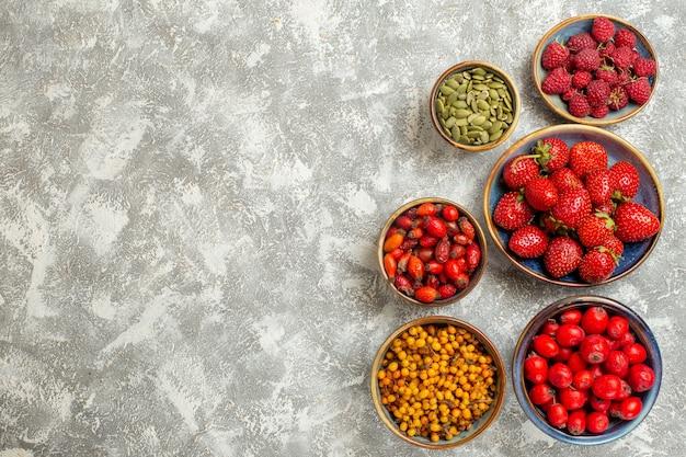 Vista superior de fresas frescas con bayas sobre fondo blanco.