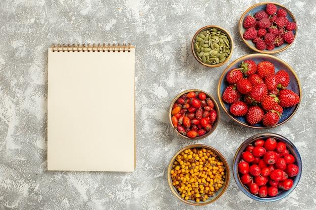 Vista superior de fresas frescas con bloc de notas y bayas sobre fondo blanco.