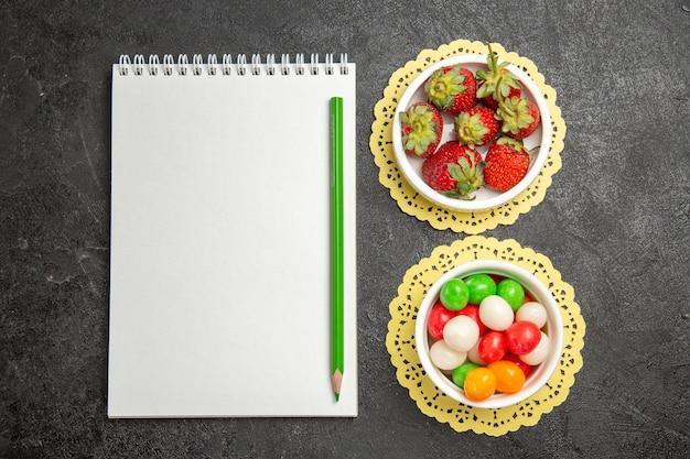 Vista superior de fresas frescas con caramelos de colores sobre fondo oscuro, fruta, baya, color, arco iris, caramelo