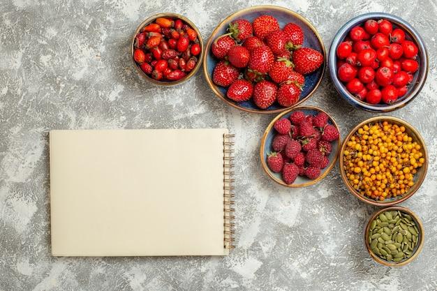 Vista superior de fresas frescas con frutos rojos sobre fondo blanco claro baya fresca