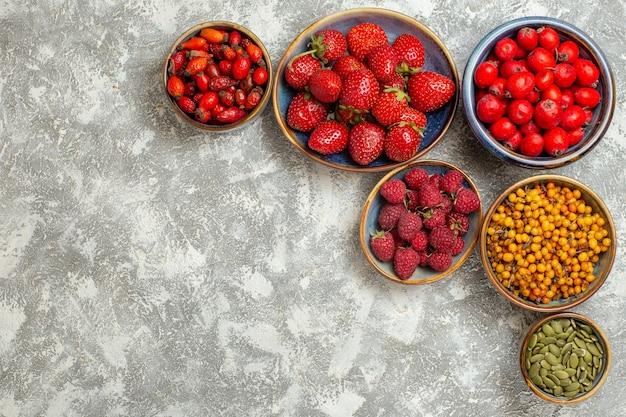 Vista superior de fresas frescas con frutos rojos sobre fondo blanco.
