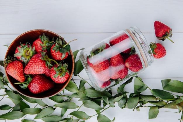 Vista superior de fresas frescas maduras en un tazón de madera y fresas esparcidas de un frasco de vidrio y hojas verdes en la mesa de madera blanca
