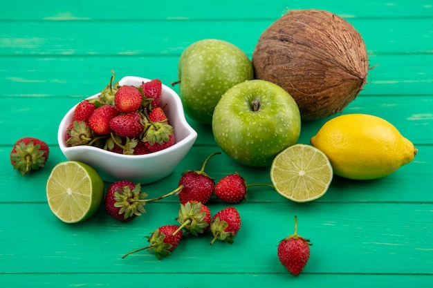 Vista superior de fresas frescas en un recipiente blanco con manzanas verdes, coco, limón, lima sobre un fondo de madera verde
