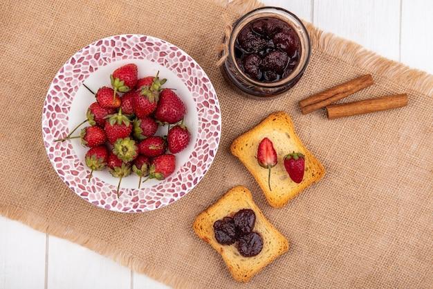 Vista superior de fresas frescas en un recipiente sobre un paño de saco con mermelada de fresa con ramas de canela sobre un fondo de madera blanca