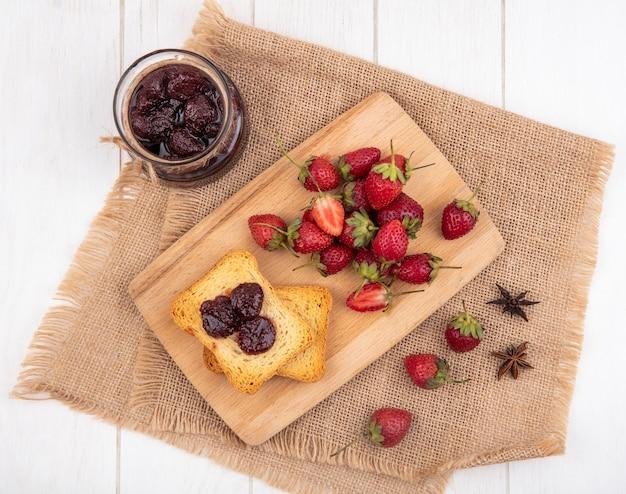 Vista superior de fresas frescas en una tabla de cocina de madera sobre un paño de saco con mermelada de fresa sobre fondo blanco.