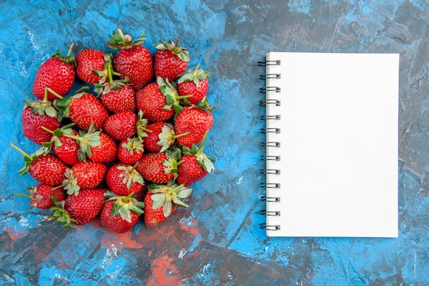 Vista superior de fresas rojas con bloc de notas sobre fondo azul.