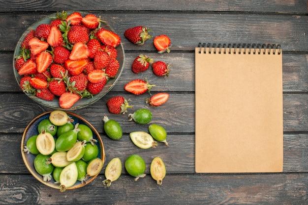 Vista superior de fresas rojas con feijoas frescas en un escritorio rústico de madera oscura.