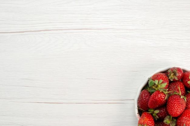 Vista superior de fresas rojas frescas bayas suaves y deliciosas dentro de la placa blanca en luz, fruta roja fresca