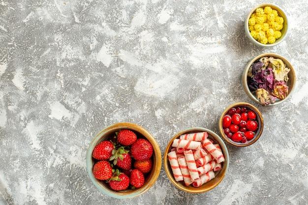 Vista superior de fresas rojas frescas con caramelos en superficie blanca color caramelo dulce de fruta