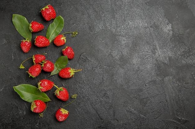 Vista superior de fresas rojas frescas en color gris oscuro de la fruta madura de la baya de la mesa