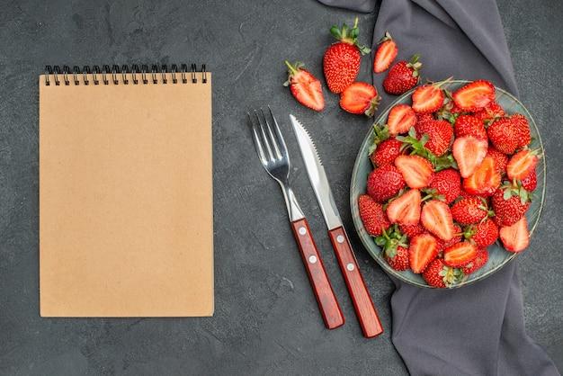 Vista superior de fresas rojas frescas dentro de la placa con el bloc de notas sobre fondo oscuro
