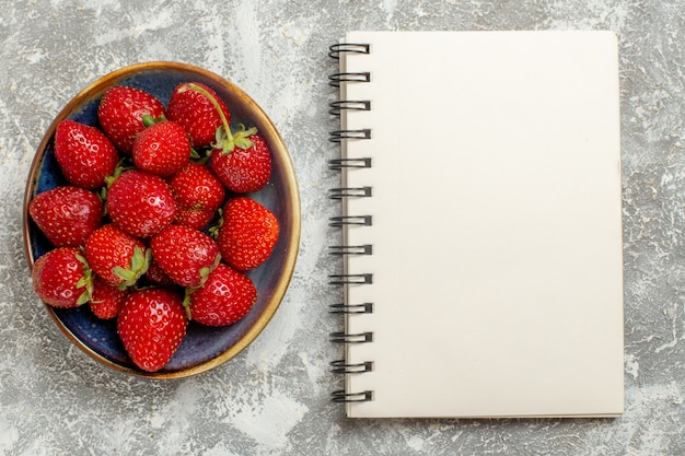 Vista superior fresas rojas frescas dentro de la placa sobre fondo blanco.