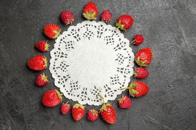 Vista superior de fresas rojas frescas forradas en frutos de baya de color oscuro de mesa