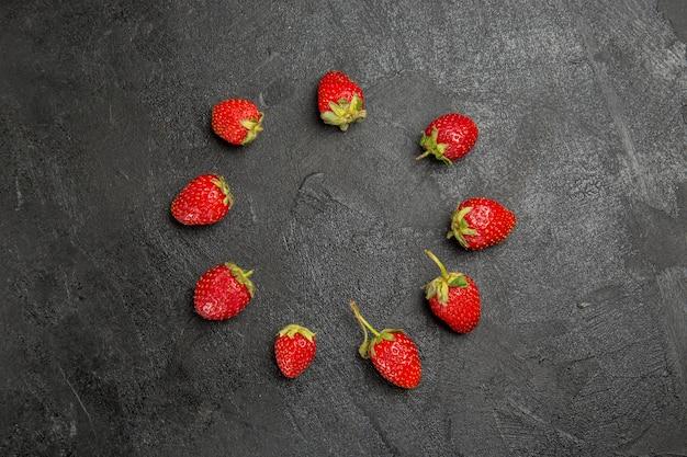 Vista superior de fresas rojas frescas forradas en mesa oscura color fruta baya madura
