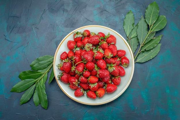 Vista superior fresas rojas frescas frutas melosas bayas dentro de la placa sobre el fondo azul oscuro baya verano suave