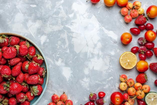 Vista superior de fresas rojas frescas con otras frutas en la mesa de luz, fruta, baya, vitamina fresca