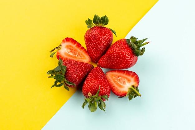 Vista superior fresas rojas jugosas suaves en el piso azul amarillo