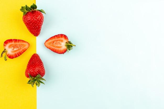 Vista superior fresas rojas jugosas suaves sobre el fondo amarillo azul