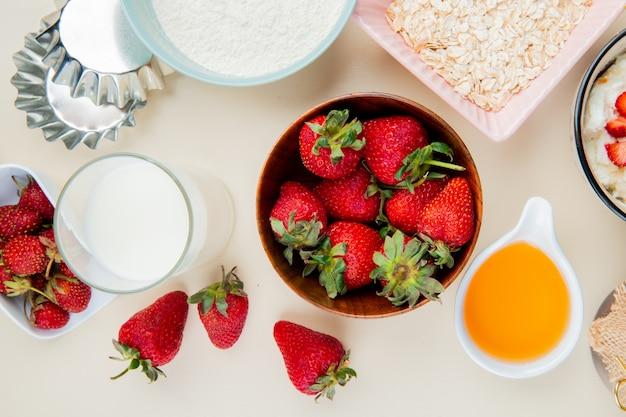 Vista superior de fresas en un tazón y vaso de leche y mantequilla derretida con harina y avena en superficie blanca