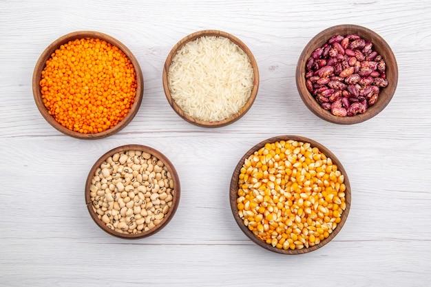 Vista superior de frijoles frescos y granos de maíz de arroz lentejas amarillas en tazones marrones sobre superficie blanca