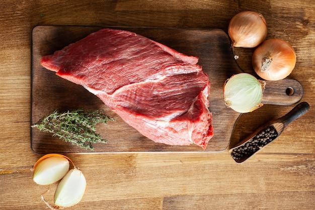 Vista superior de los frijoles de pimienta junto a un gran trozo de carne roja en corte vintage. copiar espacio disponible.