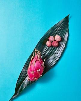 Vista superior de la fruta del dragón exótica tropical o pitaya, lichis con hojas de hoja perenne con una textura de rayas gráfica aislada sobre un fondo azul