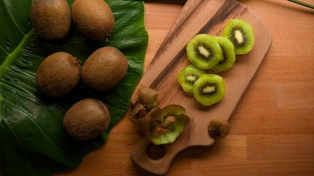Vista superior de la fruta de kiwi fresca en rodajas en la tabla de cortar y la fruta de kiwi entera en la mesa de la cocina