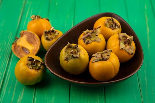 Vista superior de frutas de caqui frescas y saludables en un recipiente sobre una mesa de madera verde