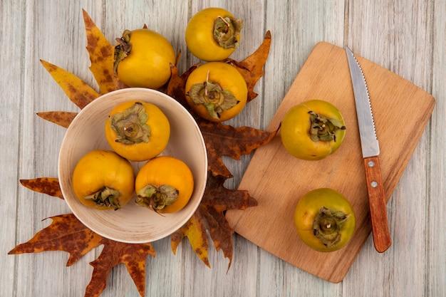 Vista superior de frutas de caqui en un recipiente con hojas con frutas de caqui en una tabla de cocina de madera con cuchillo sobre una mesa de madera gris