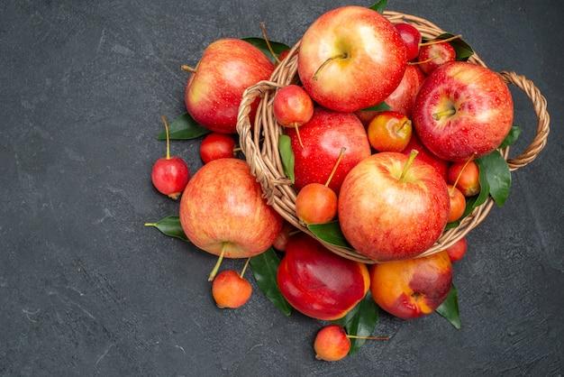 Vista superior frutas cerezas rojas-amarillas y manzanas con hojas en la canasta