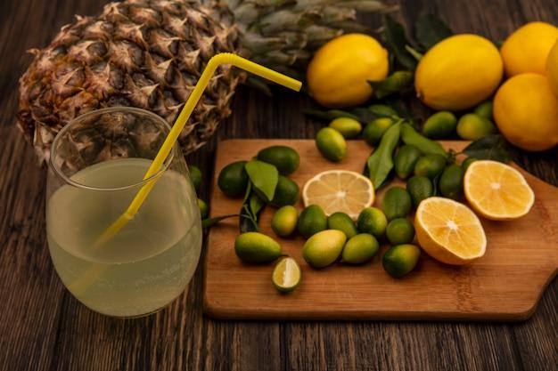 Vista superior de frutas como limones y kinkans en una tabla de cocina de madera con jugo de limón fresco en un vaso con piña aislado en una superficie de madera