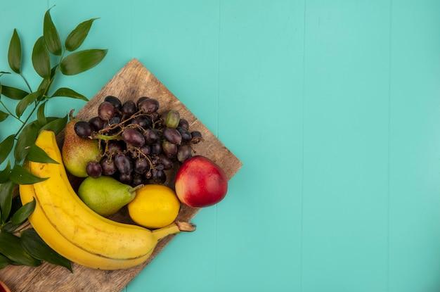 Vista superior de frutas como melocotón pera limón uva plátano con hojas sobre tabla de cortar sobre fondo azul con espacio de copia