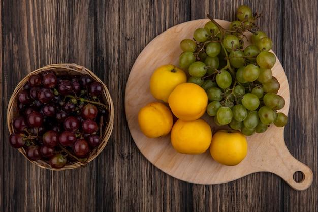 Vista superior de frutas como nectacots y uva blanca en tabla de cortar con canasta de uva negra sobre fondo de madera