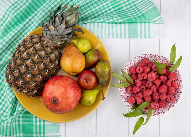 Vista superior de frutas como piña granada durazno en placa sobre tela escocesa con frambuesas en un tazón sobre superficie de madera