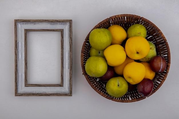 Vista superior de frutas como pluots y nectacots en canasta con marco sobre fondo blanco con espacio de copia