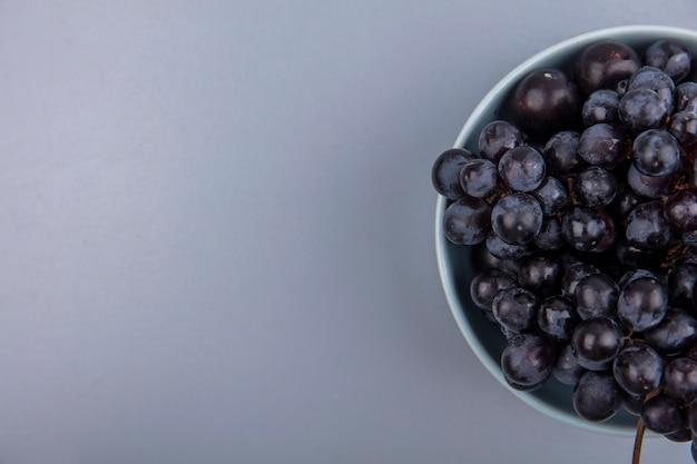 Vista superior de frutas como uva y endrinas en un recipiente sobre fondo gris con espacio de copia