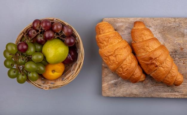 Vista superior de frutas como uva nectacot pluot en canasta y croissants en tabla de cortar sobre fondo gris
