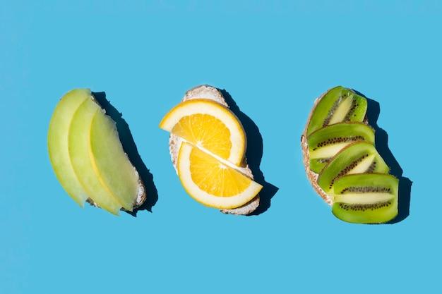 Vista superior de frutas exóticas en pan sobre fondo azul.
