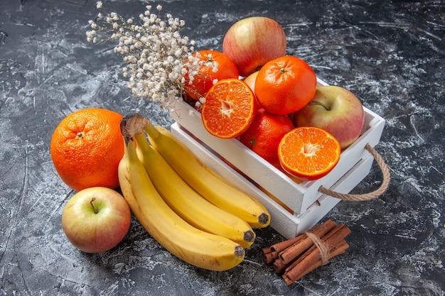 Vista superior de frutas frescas en caja palitos de canela sobre fondo gris
